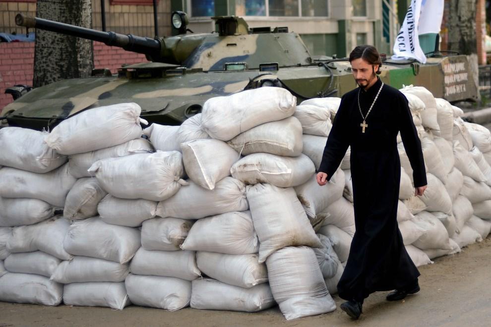 7.UKRAINA, Sławiańsk, 23 kwietnia 2014: Duchowny mija barykadę przed siedzibą SBU. AFP PHOTO/KIRILL KUDRYAVTSEV