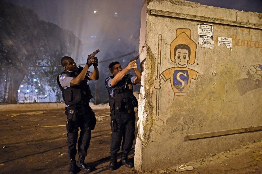 8.BRAZYLIA, Rio de Janeiro, 22 kwietnia 2014: Policjanci wchodzą do faweli w pobliżu Copacabany. AFP PHOTO / CHRISTOPHE SIMON