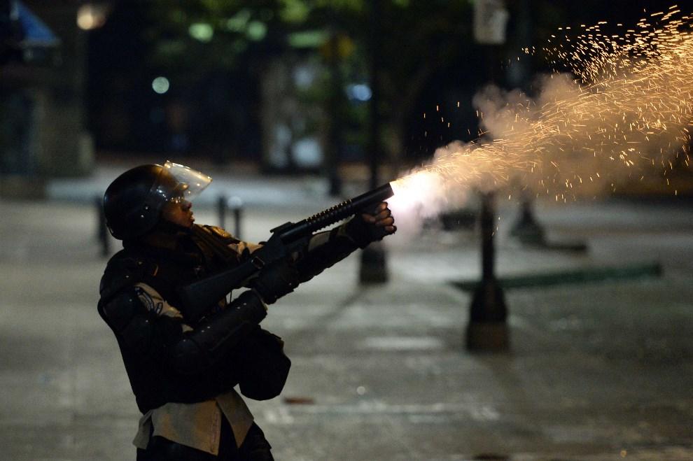 8.WENEZUELA, Caracas, 7 kwietnia 2014: Policjant strzela pojemnikami z gazem łzawiącym w kierunku protestującej grupy. AFP PHOTO/JUAN BARRETO