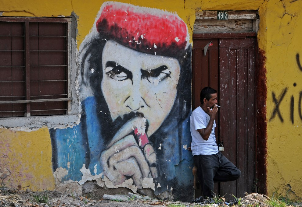 """9.HONDURAS, Santa Barbara, 18 kwietnia 2014: Mężczyzna, na tle wizerunku """"Che"""" Guevary, przygląda się procesji wielkopiątkowej. AFP PHOTO/Orlando SIERRA"""