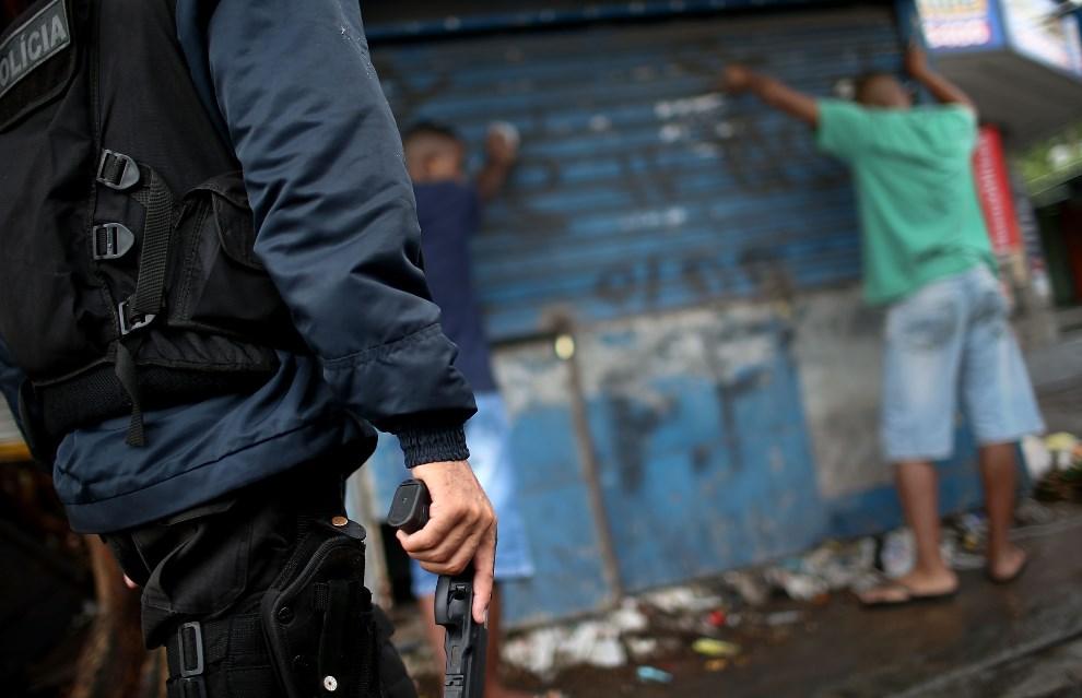 9.BRAZYLIA, Rio de Janeiro, 23 marca 2014: Policjant podczas przeszukiwania zatrzymanych mieszkańców faweli. (Foto: Mario Tama/Getty Images)