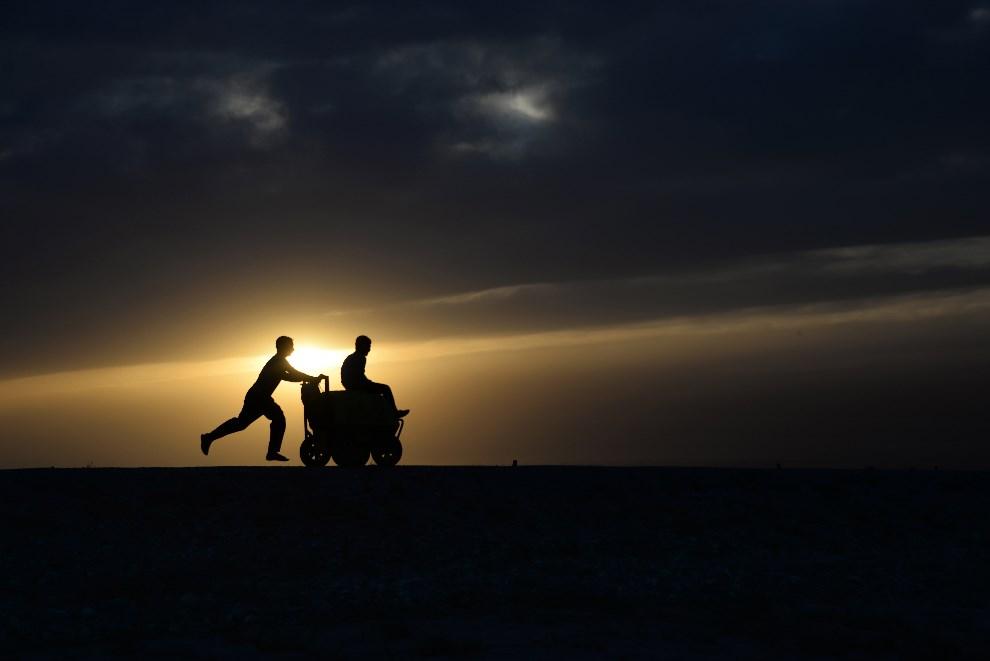 10.AFGANISTAN, Mazar-i-Sharif, 16 maja 2014: Chłopcy z wózkiem do sprzedaży lodów. AFP PHOTO/FARSHAD USYAN
