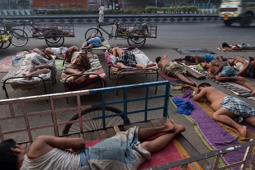 10.INDIE, Kolkata, 24 maja 2014: Mężczyźni odpoczywający podczas fali upałów. AFP PHOTO/ Dibyangshu Sarkar
