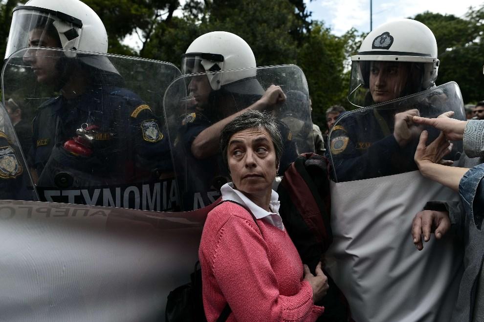 10.GRECJA, Ateny, 6 maja 2014: Protestująca kobieta zatrzymywana przez policję. AFP PHOTO / ARIS MESSINIS
