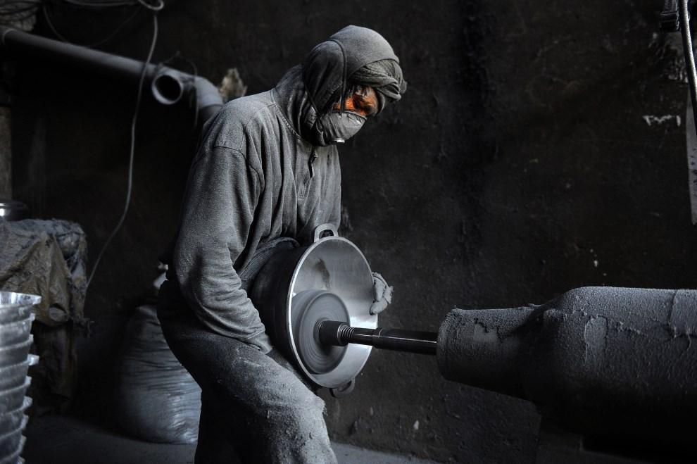 11.AFGANISTAN, Herat, 27 maja 2014: Mężczyzna pracujący przy obróbce aluminium. AFP PHOTO/AREF KARIMI