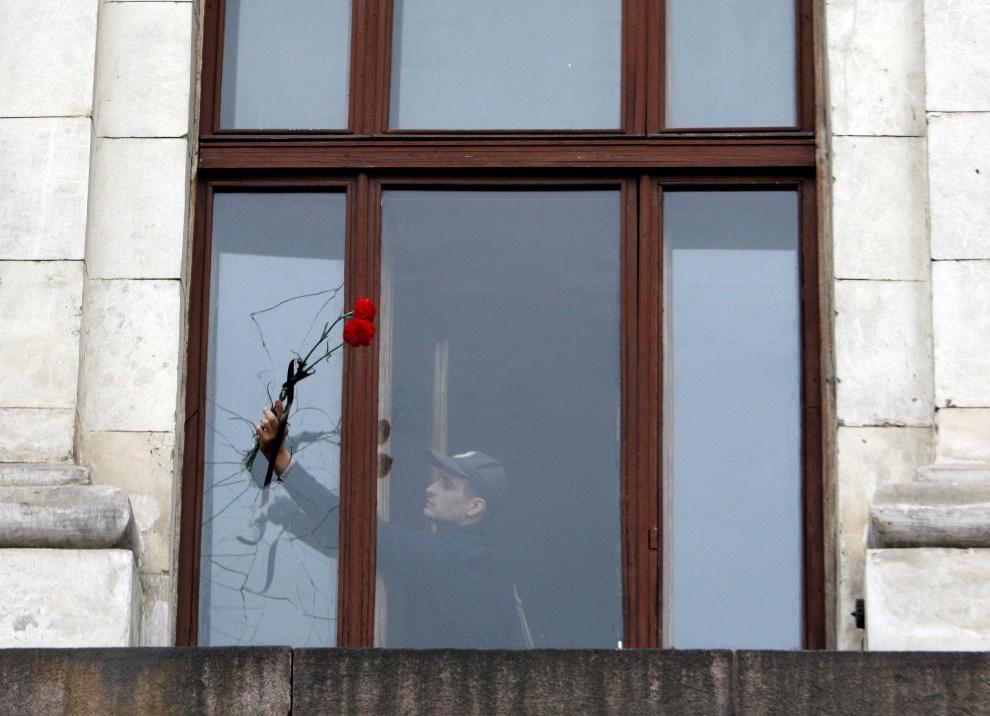11.UKRAINA, Odessa, 4 maja 2014: Mężczyzna z kwiatami w zniszczonym budynku związków zawodowych. AFP PHOTO / ANATOLII STEPANOV