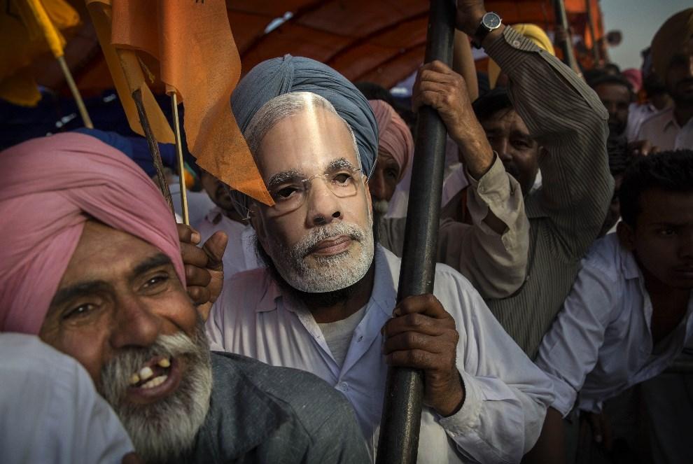12.INDIE, Bathinder, 25 kwietnia 2014: Mężczyzna w masce z podobizną Narendry Modi. (Foto: Kevin Frayer/Getty Images)