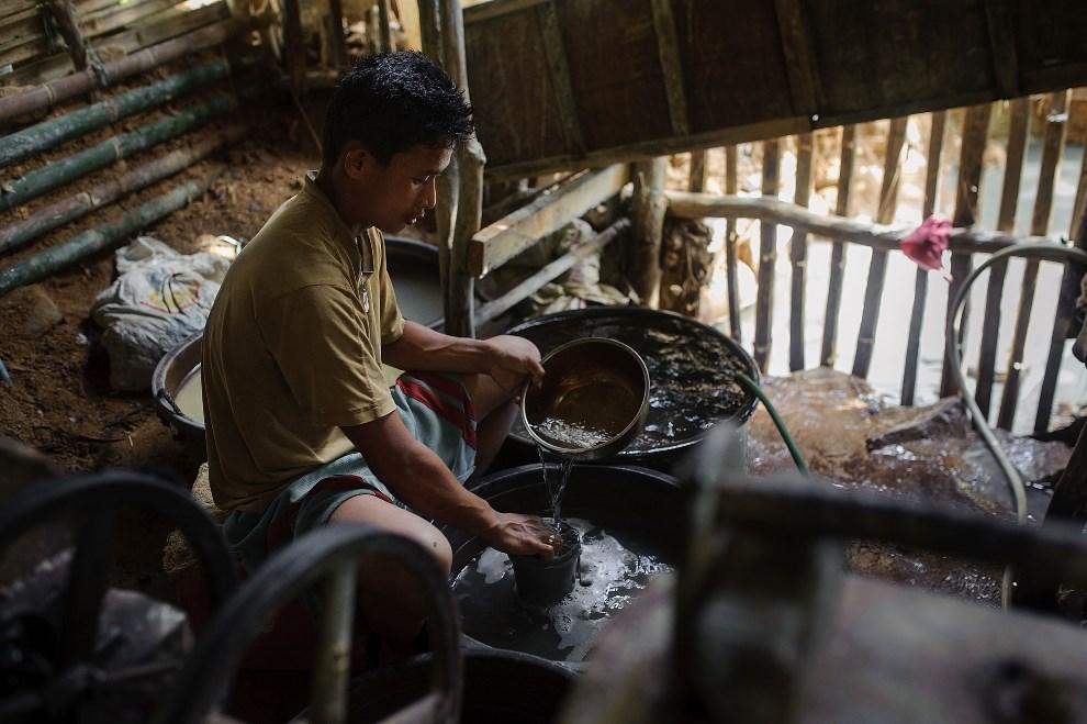 12.FILIPINY, Pinut-An, 23 kwietnia 2014: Mężczyzna przygotowuje miksturę z wody i rtęci. (Rtęć przyciąga czostki złota i oddziela je od bezwartościowej skały).   (Foto: Luc Forsyth/Getty Images)
