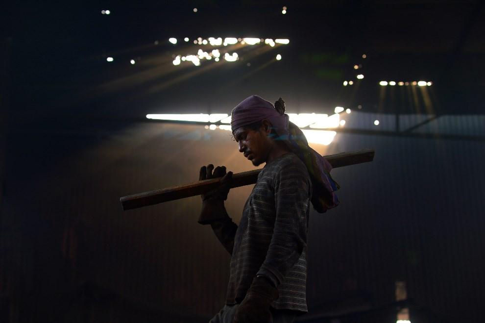 14.PAKISTAN, Lahore, 30 kwietnia 2014: Pracownik huty podczas przerwy w pracy. AFP PHOTO/Arif ALI