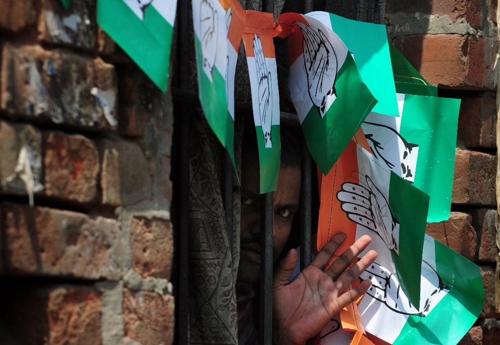 16.INDIE, Waranasi, 10 maja 2014: Mieszkaniec przedmieść wygląda przez okno ozdobione ulotkami Partii Kongresu. AFP PHOTO/ROBERTO SCHMIDT