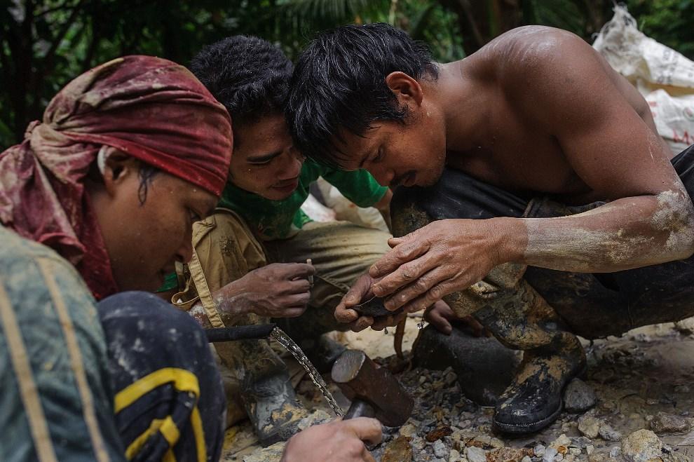 16.FILIPINY, Pinut-An, 23 kwietnia 2014: Górnicy oceniają jakość skruszonej skały. (Foto: Luc Forsyth/Getty Images)