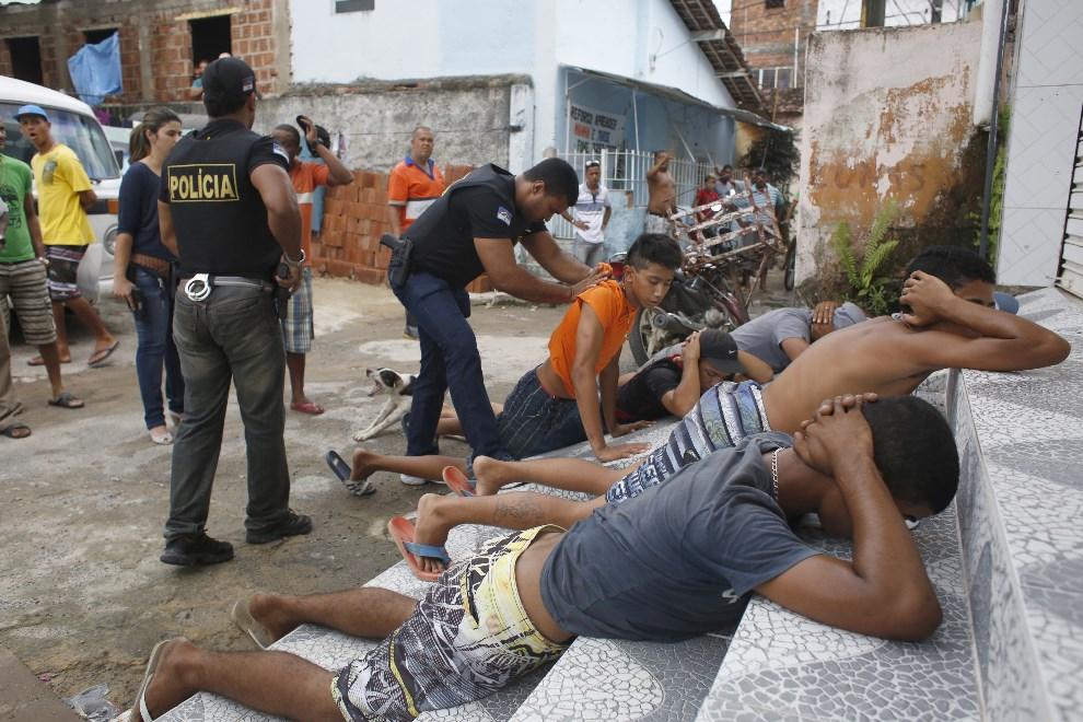 17.BRAZYLIA, Recife, 15 maja 2014: Policjanci zatrzymują mężczyzn podejrzanych o plądrowanie mieszkań. AFP PHOTO/IGO BIONE/JC Imagem