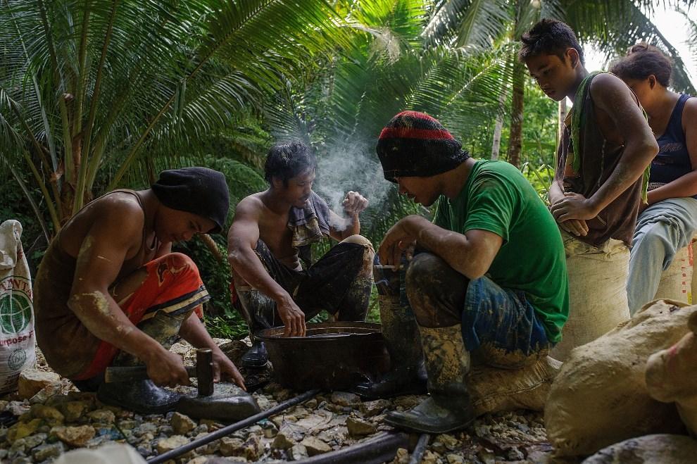 17.FILIPINY, Pinut-An, 23 kwietnia 2014: Mężczyźni kruszący skałę wydobytą z szybu. (Foto: Luc Forsyth/Getty Images)
