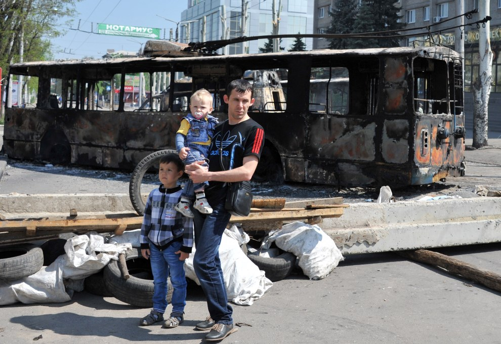 18.UKRAINA, Kramatorsk, 4 maja 2014: Mężczyzna z dziećmi w pobliżu spalonego trolejbusu. AFP PHOTO / GENYA SAVILOV