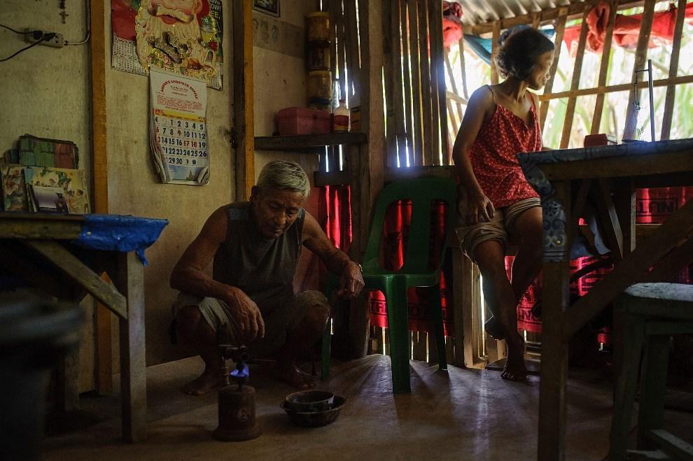 18.FILIPINY, Pinut-An, 23 kwietnia 2014: Gil Mercado, właściciel kopalni, przygotowuje palnik. Złoty pył trzymany jest w wysokiej temperaturze, aby pozbyć się   wszystkich zanieczyszczeń przed zważeniem. (Foto: Luc Forsyth/Getty Images)