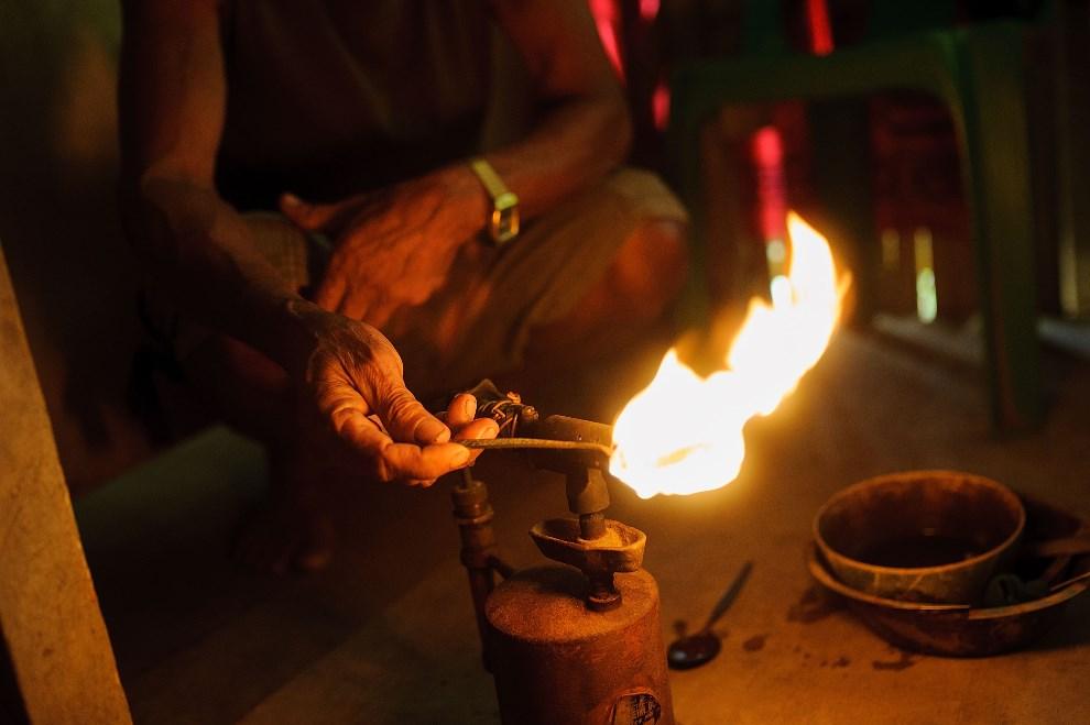 19.FILIPINY, Pinut-An, 23 kwietnia 2014: Bryłka złota rozgrzewana w ogniu palnika. (Foto: Luc Forsyth/Getty Images)