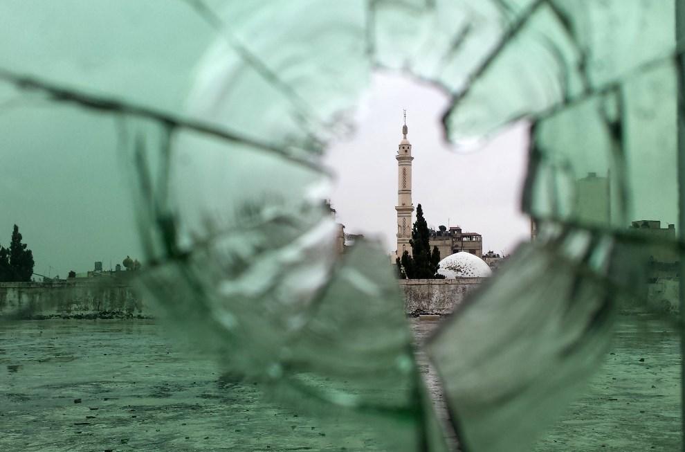 1.SYRIA, Homs, 8 maja 2014: Meczet widziany przez rozbitą szybę ostrzelanego budynku w starej części miasta. AFP PHOTO/YOUSSEF KARWASHAN