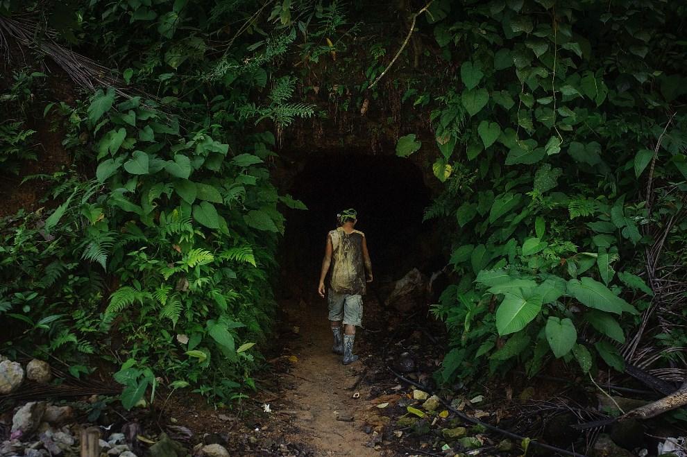 1.FILIPINY, Pinut-An, 22 kwietnia 2014: Czternastoletni górnik wchodzący do szybu. (Foto: Luc Forsyth/Getty Images)