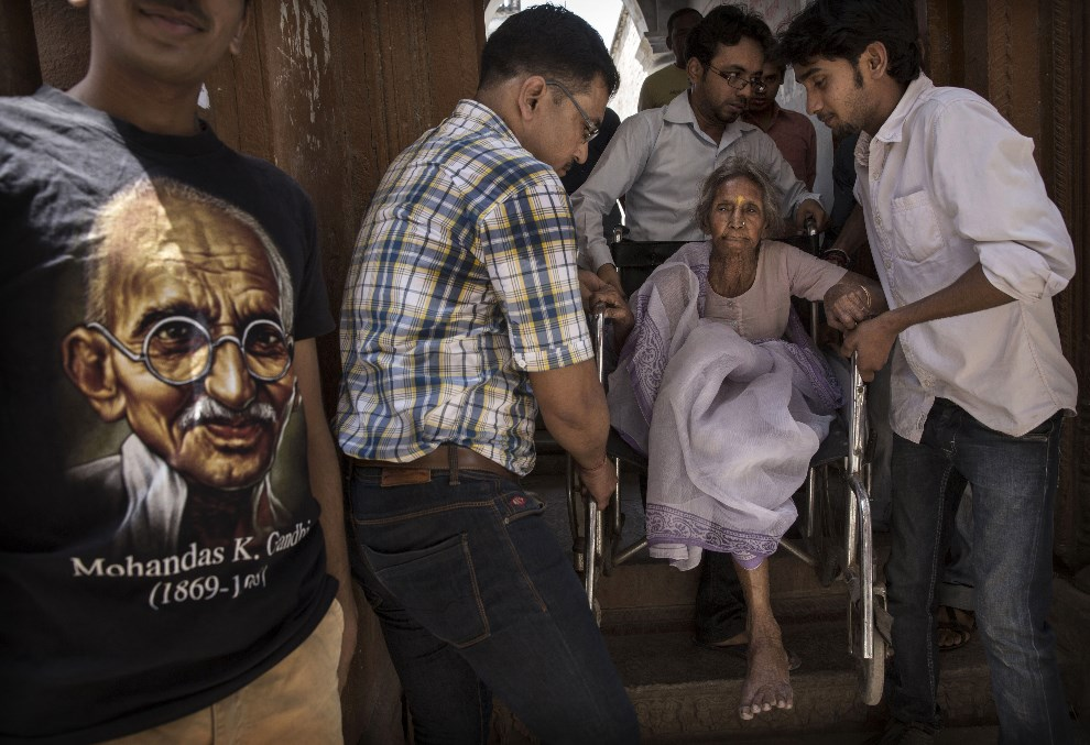 1.INDIE, Waranasi, 12 maja 2014: Bliscy i pracownicy komisji pomagają starszej kobiecie wejść do lokalu wyborczego. (Foto: Kevin Frayer/Getty Images)