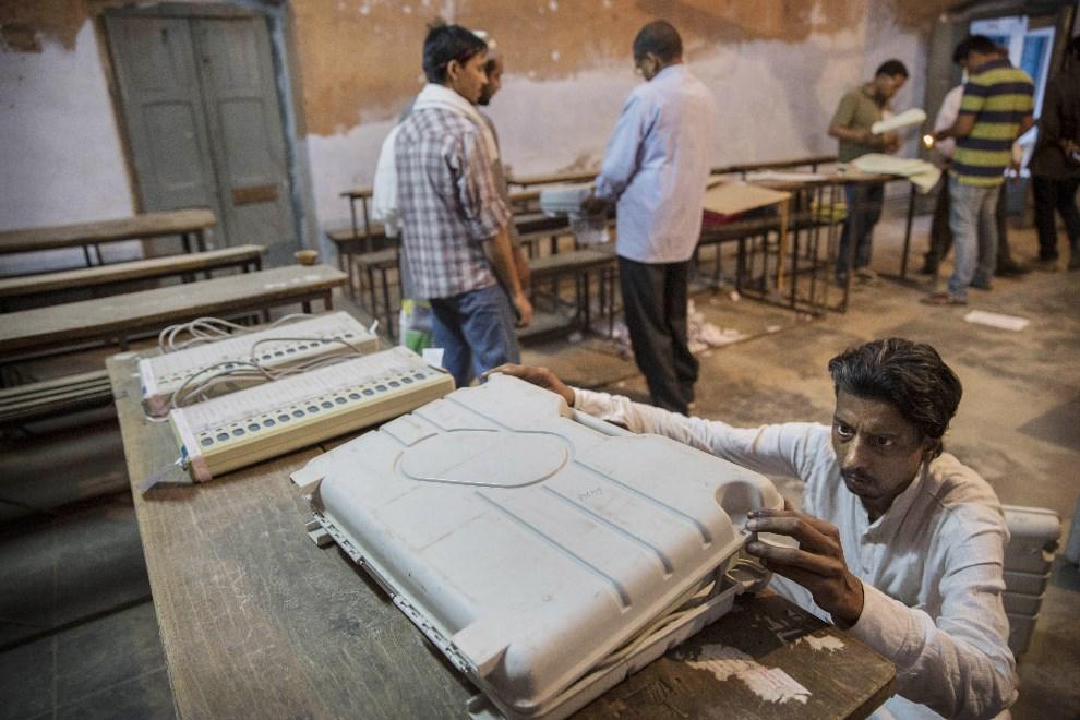 20.INDIE, Waranasi, 12 maja 2014: Członek komisji wyborczej zamyka urządzenia do elektronicznego głosowania. (Foto: Kevin Frayer/Getty Images)
