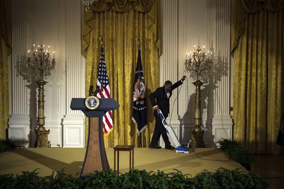 21.USA, Waszyngton, 5 maja 2014: Mężczyzna odkurza podest na których wystąpi prezydent USA. AFP PHOTO/Brendan SMIALOWSKI