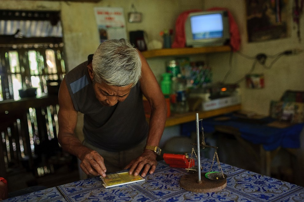 21.FILIPINY, Pinut-An, 23 kwietnia 2014: Właściciel kopalni oblicza wartość pozyskanego złota. (Foto: Luc Forsyth/Getty Images)