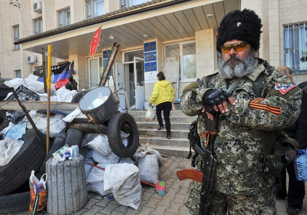 22.UKRAINA, Kramatorsk, 6 maja 2014: Prorosyjski bojownik przed jednym z budynków rządowych. AFP PHOTO/ GENYA SAVILOV