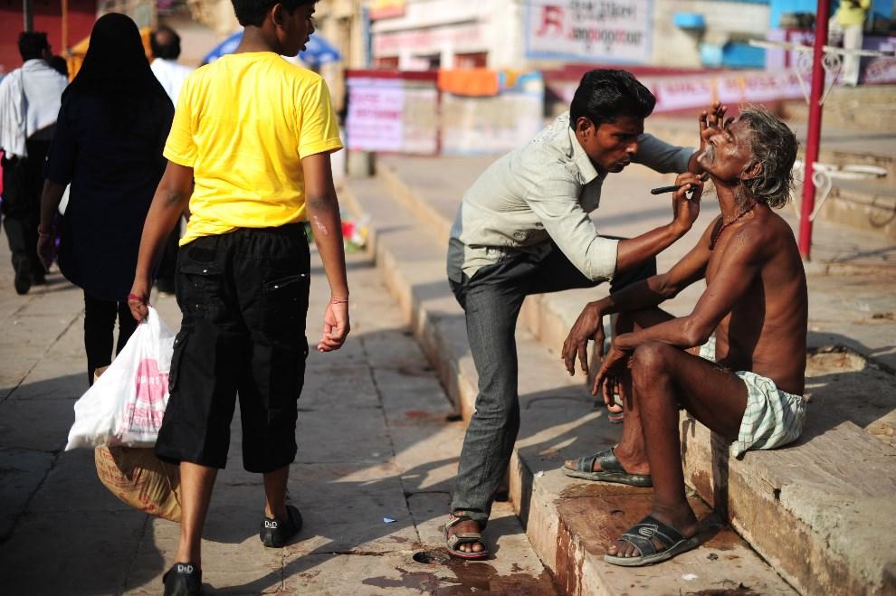23.INDIE, Waranasi, 11 maja 2014: Mężczyzna korzystający z usług ulicznego fryzjera. AFP PHOTO/ROBERTO SCHMIDT