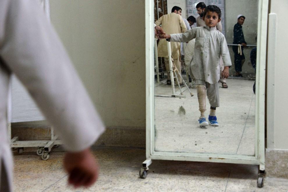 24.AFGANISTAN, Jalalabad, 3 maja 2014: Chłopiec przymierzający nową protezę. AFP  PHOTO/Noorullah Shirzada
