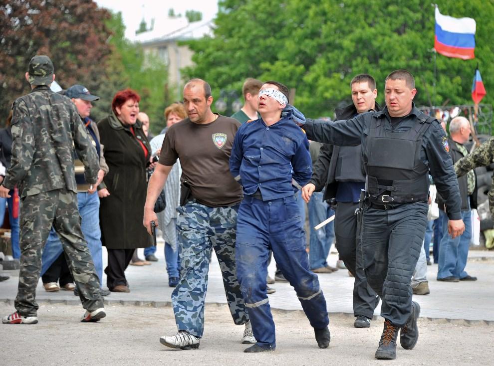 24.UKRAINA, Donieck, 5 maja 2014: Prorosyjscy bojownicy wyprowadzają mężczyznę z przejętego budynku. AFP PHOTO/ GENYA SAVILOV
