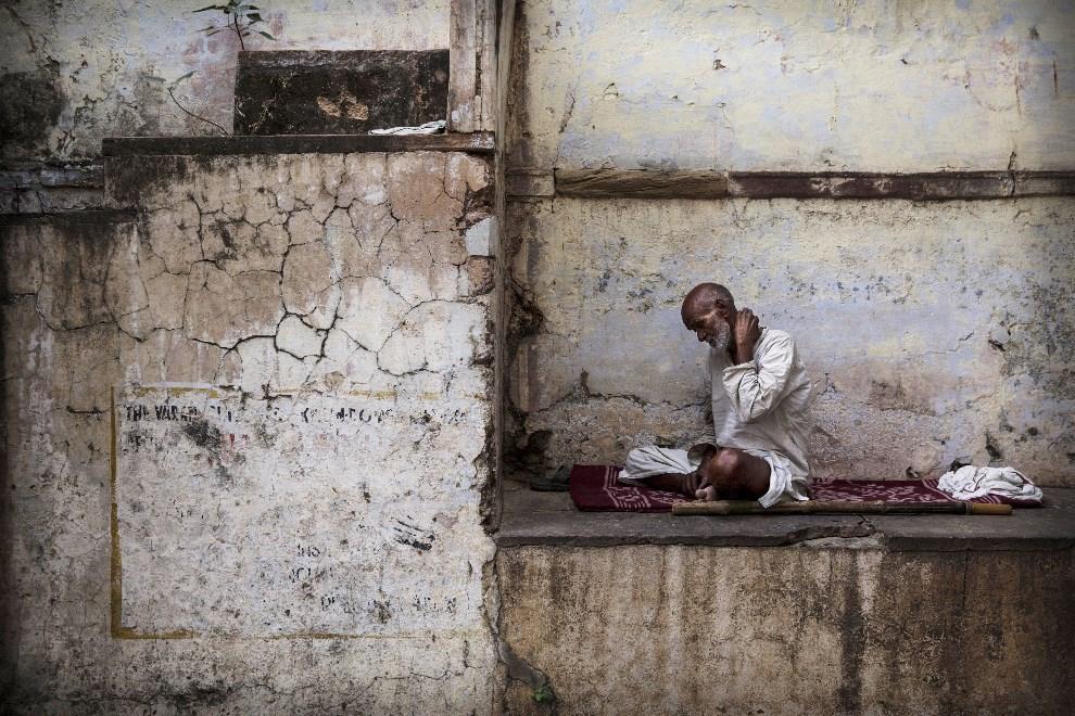 24.INDIE, Waranasi, 11 maja 2014: Mężczyzna siedzący w alejce. (Foto: Kevin Frayer/Getty Images)