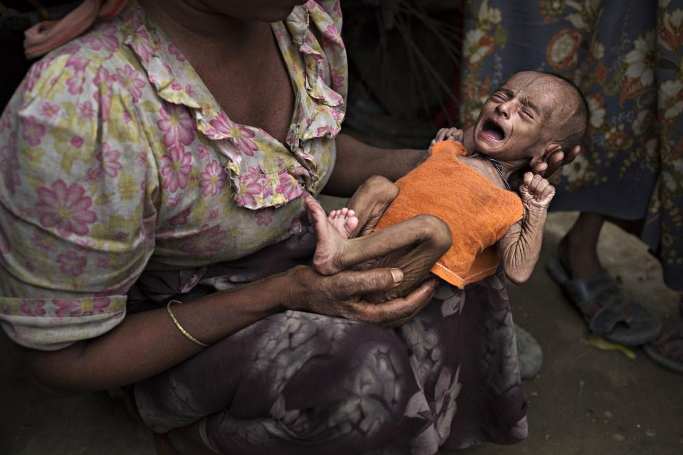 25.MJANMA, Sittwe, 6 maja 2014: Kobieta żebrząca o pomoc trzyma na rękach swoje niedożywione dziecko. (Foto: Andre Malerba/Getty Images)
