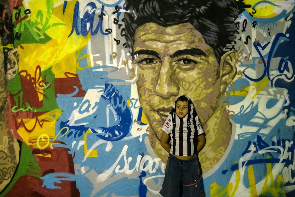 26.BRAZYLIA, Resende, 21 maja 2014: Chłopiec na tle muralu z podobiznami piłkarzy drużyny narodowej. AFP PHOTO / YASUYOSHI CHIBA