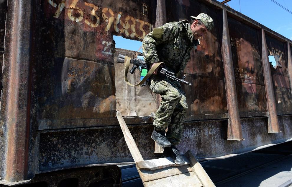 26.UKRAINA, Słowiańsk, 6 maja 2014: Prorosyjski bojownik zajmuje pozycję w pobliżu torów kolejowych. AFP PHOTO / VASILY MAXIMOV