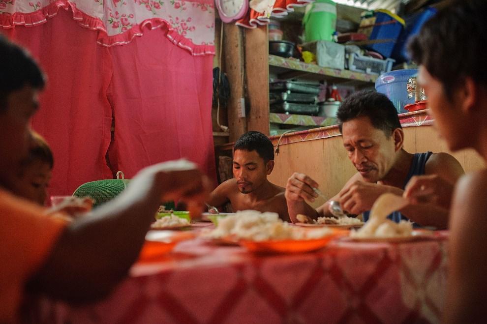 26.FILIPINY, Pinut-An, 22 kwietnia 2014: Górnicy, razem z rodzinami podczas posiłku. (Foto: Luc Forsyth/Getty Images)
