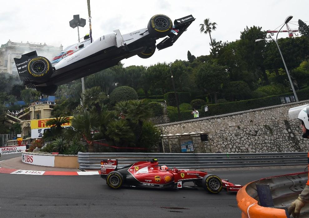 27.MONAKO, Monte-Carlo, 25 maja 2014: Kimi Raikkonen mija bolid usuwany z toru przez dźwig. AFP PHOTO / ANNE-CHRISTINE POUJOULAT