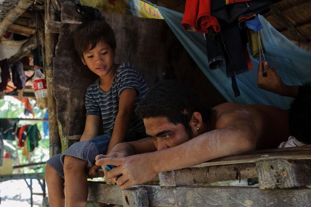 28.FILIPINY, Pinut-An, 22 kwietnia 2014: Mężczyzna z telefonem komórkowym podczas odpoczynku. (Foto: Luc Forsyth/Getty Images)