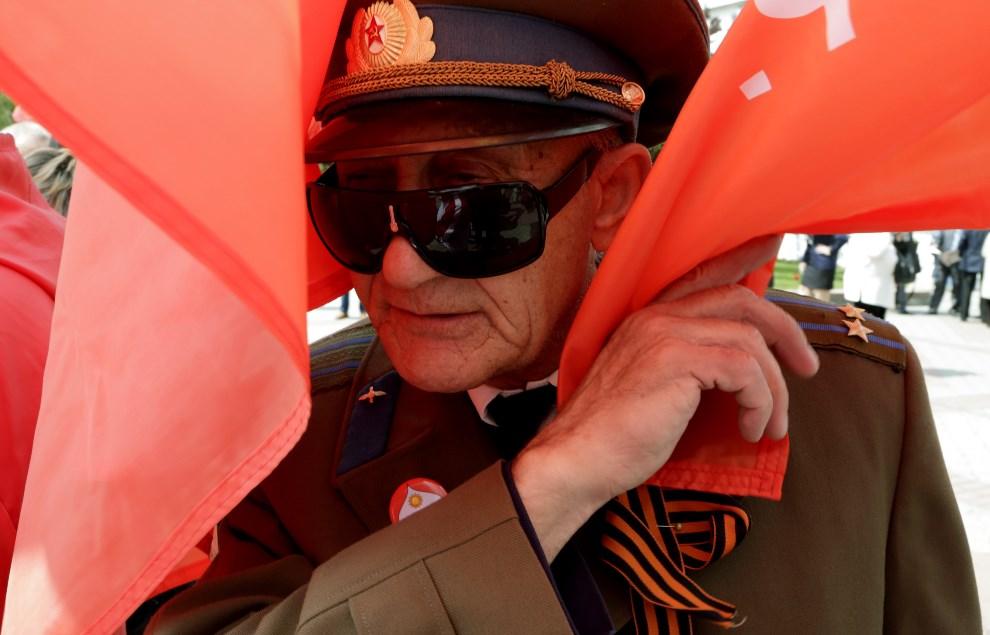 2.UKRAINA, Symferopol. 6 maja 2014: Weteran wojenny z komunistyczną flagą. AFP PHOTO/ MAX VETROV