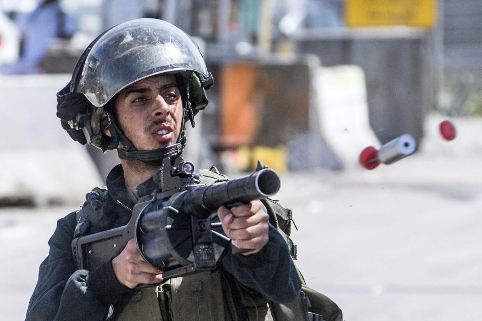 2.ZAHODNI BRZEG, Kalandia, 15 maja 2014: Izraelski żołnierz ostrzeliwuje protestujących Palestyńczyków pojemnikami z gazem łzawiącym. AFP PHOTO / JACK   GUEZ