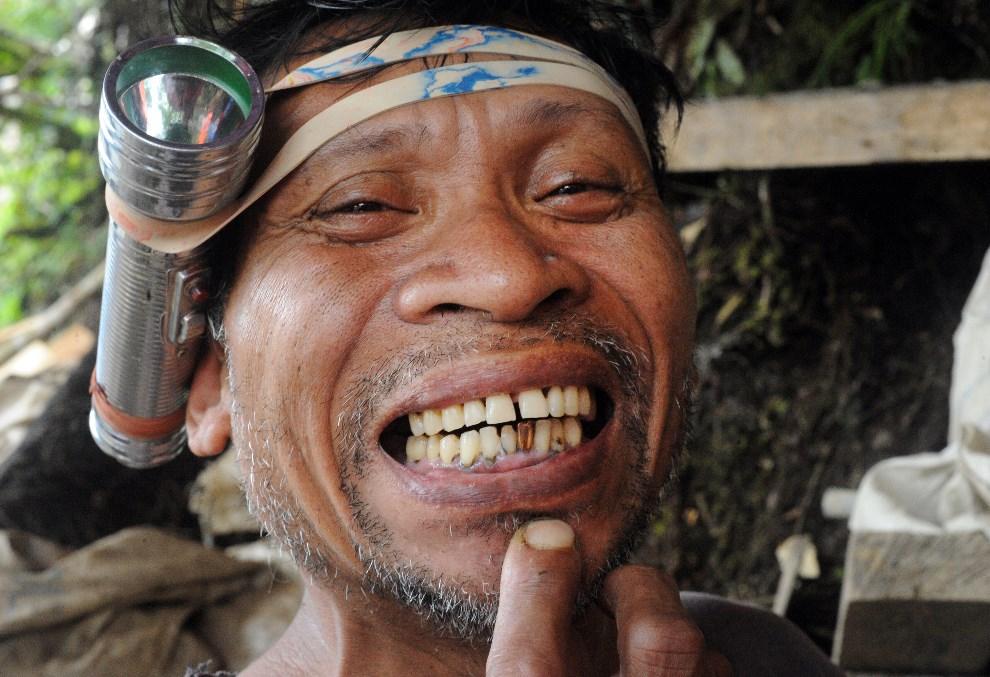 30.FILIPINY, Mt. Diwata, 17 lipca 2013: Mężczyzna pokazuje złotego zęba zrobionego z własnoręcznie pozyskanego kruszcu. AFP PHOTO / TED ALJIBE