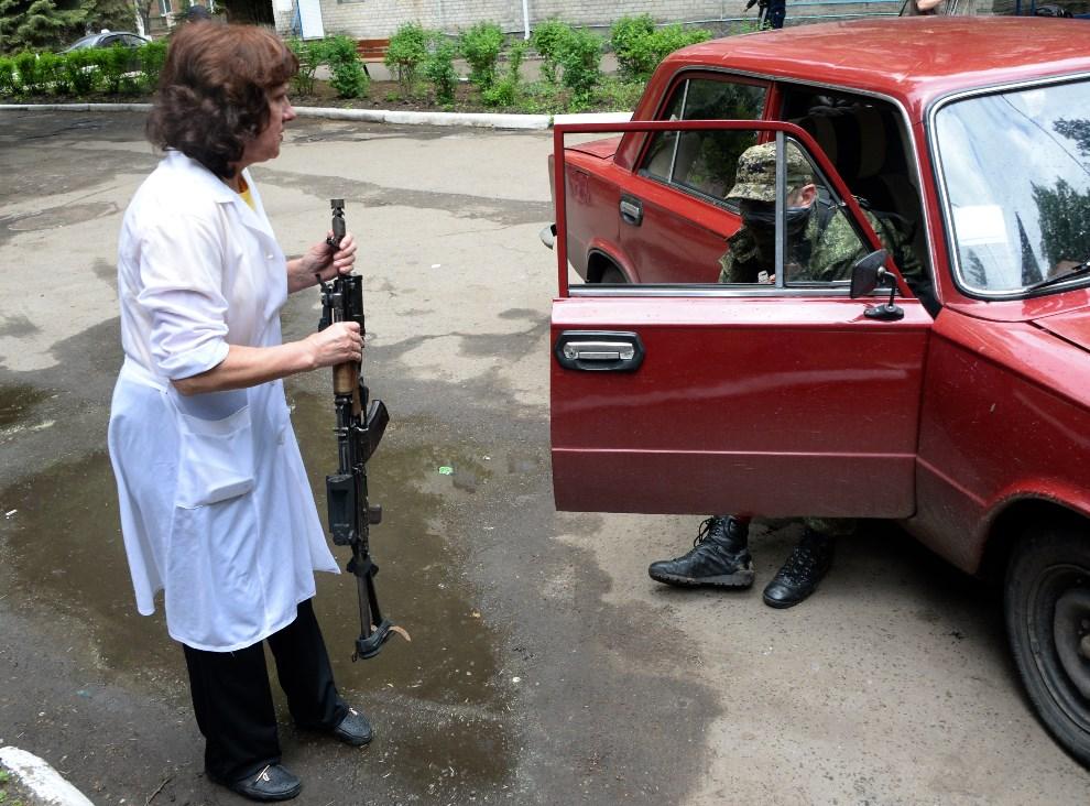 34.UKRAINA, Słowiańsk, 5 maja 2014: Pracownica szpitala trzyma karabin prorosyjskiego bojownika rannego podczas walk w mieście. AFP PHOTO / VASILY MAXIMOV