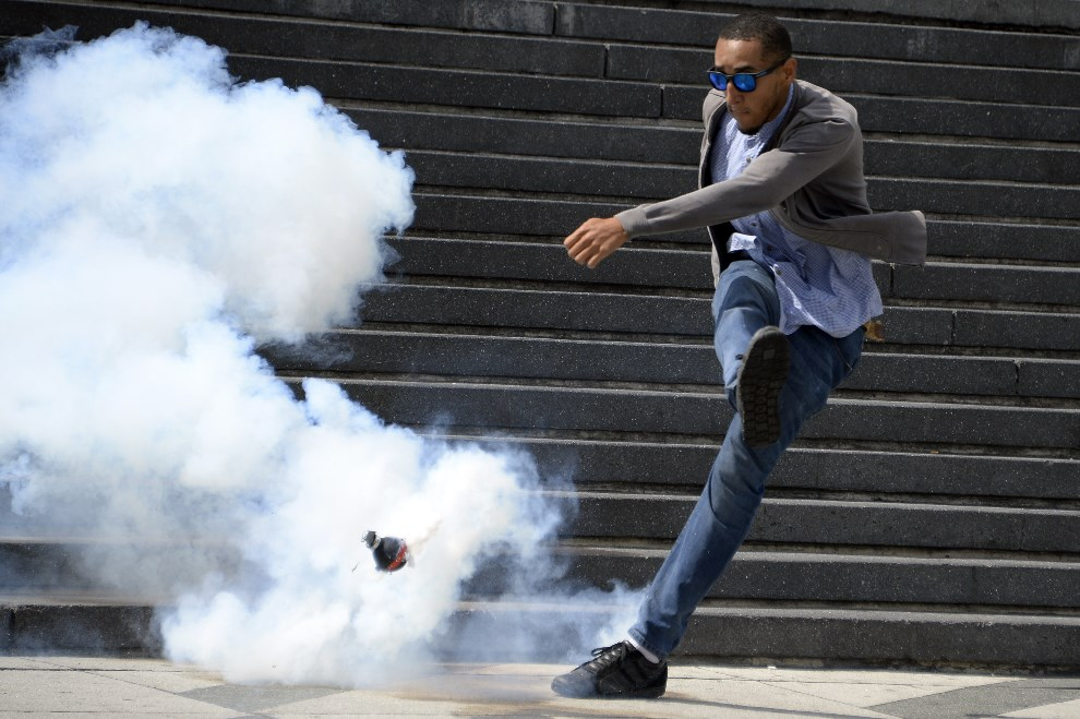 3.WENEZUELA, Caracas, 14 maja 2014: Uczestnik antyrządowych protestów wykopuje pojemnik z gazem łzawiącym. AFP PHOTO/JUAN BARRETO