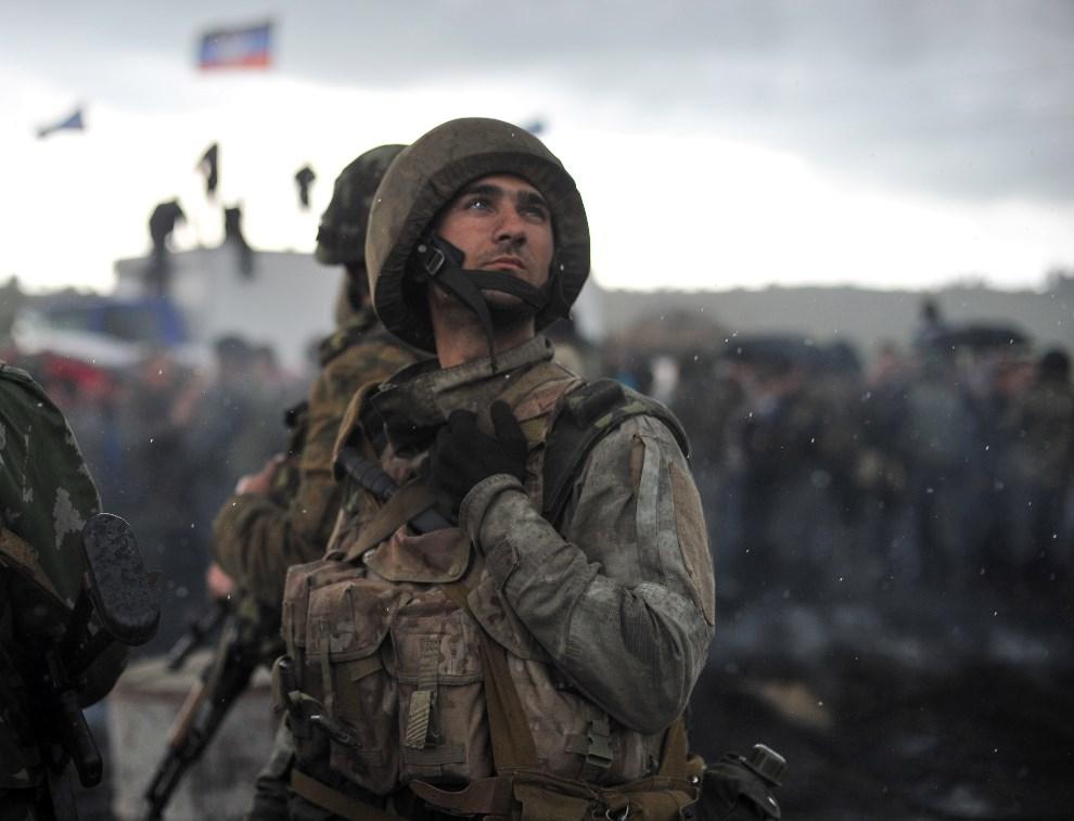 42.UKRAINA, Słowiańsk, 2 maja 2014: Ukraiński żołnierz przygląda się barykadzie wnoszonej na drodze łączącej Słowiańsk z Kramatorskiem. AFP PHOTO/ GENYA SAVILOV