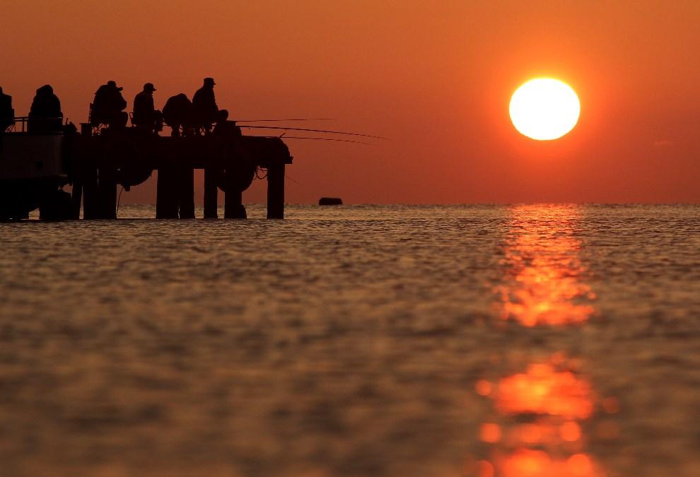43.UKRAINA, Ałuszta, 4 maja 2014: Wędkarze w porcie na tle zachodzącego słońca. AFP PHOTO / YURI LASHOV