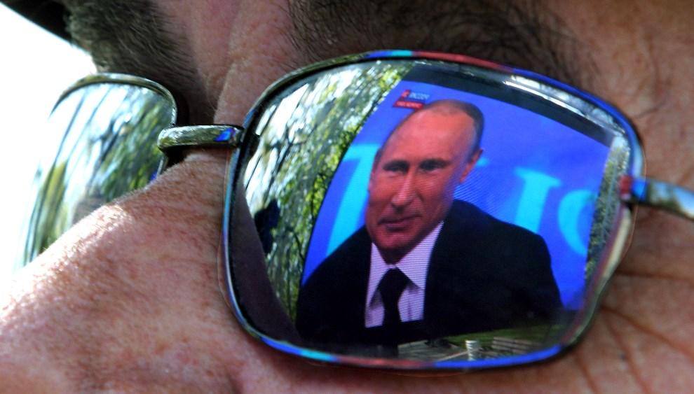 4.UKRAINA, Sewastopol, 17 kwietnia 2014: Obraz telewizyjny odbija się w okularach mieszkańca Sewastopola. AFP PHOTO/ YURIY LASHOV