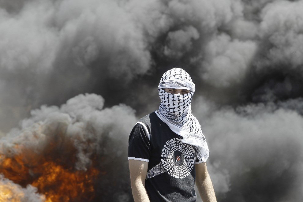 5.ZACHODNI BRZEG, Kfar Qaddum, 2 maja 2014: Palestyńczyk na tle płonących opon podczas demonstracji przeciw ekspansji terytorialnej Izraela. AFP PHOTO/JAAFAR   ASHTIYEH