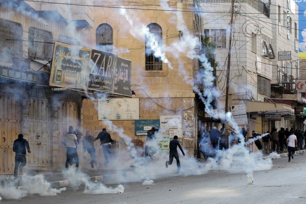 5.ZACHODNI BRZEG, Hebron, 8 maja 2014: Palestyńczycy chronią się przed spadającymi pojemnikami z gazem łzawiącym. AFP PHOTO/ HAZEM BADER