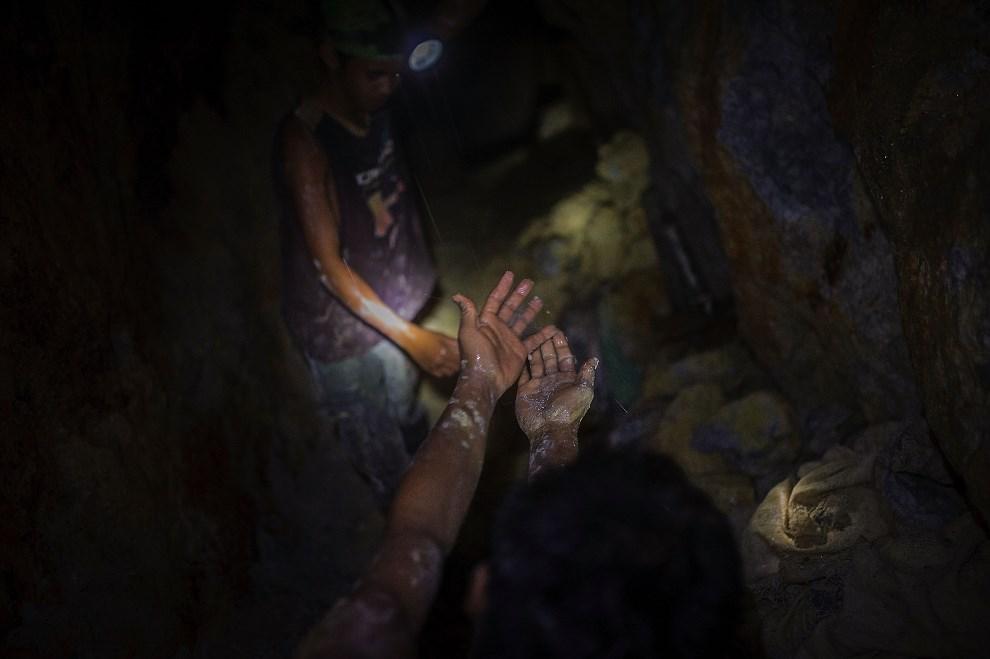 5.FILIPINY, Pinut-An, 22 kwietnia 2014: Mężczyzna opłukuje dłonie w wodzie kapiącej z sufitu szybu. (Foto: Luc Forsyth/Getty Images)
