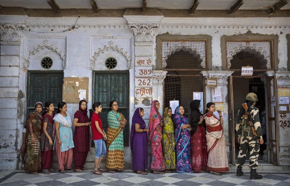 5.INDIE, Waranasi, 12 maja 2014: Policjant pilnuje porządku w kolejce do lokalu wyborczego. (Foto: Kevin Frayer/Getty Images)