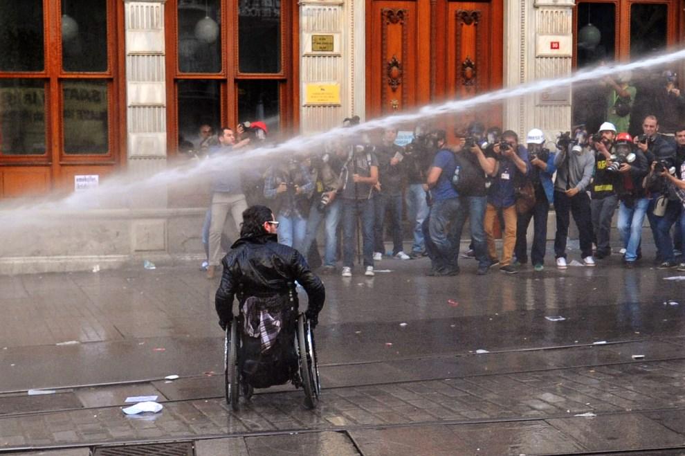 6.TURCJA, Stambuł, 14 maja 2014: Mężczyzna na wózku, fotografowany przez grupę dziennikarzy, podczas zamieszek. AFP PHOTO/OZAN KOSE